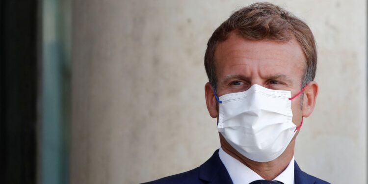 French President Emmanuel Macron, wearing a protective face mask, waits for the arrival of Madagascar