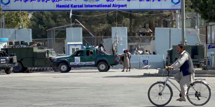 Taliban stand at the entrance gate of Hamid Karzai International airport while Taliban forces block the roads around the airport after yesterday